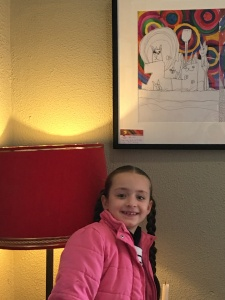 Naomi - young artist posing with her painting